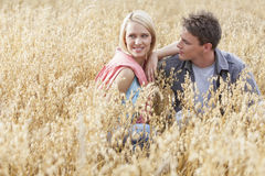Beautiful young woman looking away while sitting with boyfriend amidst field Royalty Free Stock Photos