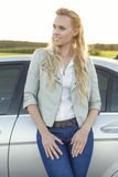 Beautiful young woman looking away while standing by car at countryside Stock Photos