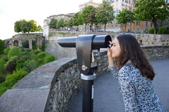 Beautiful young woman looking at Bergamo lower city through touristic telescope Stock Images