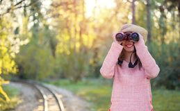 Beautiful young woman looking through binoculars in the nature stock photography