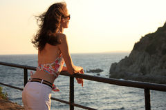 Beautiful young woman looking at boundless sea. And mountains Stock Photography