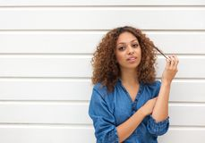 Beautiful young woman looking at camera with hand in hair Royalty Free Stock Photography