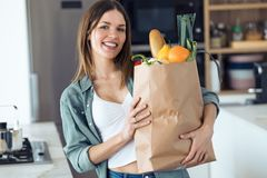 Beautiful young woman looking at camera while holding shopping bag with fresh vegetables in the kitchen at home. Portrait of beautiful young woman looking at stock photo