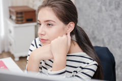 Beautiful young woman looking at a computer screen and thinking Royalty Free Stock Photography