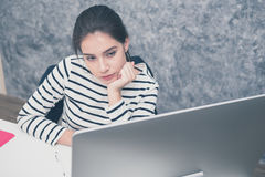 Beautiful young woman looking at a computer screen and thinking at the office stock images