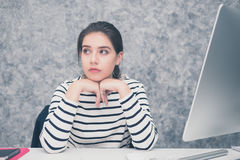 Beautiful young woman looking at a computer screen and thinking at the office royalty free stock photos