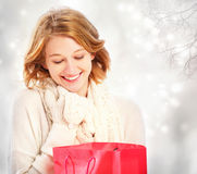 Beautiful young woman looking at a gift bag. Beautiful young woman looking at a red gift bag Royalty Free Stock Photos