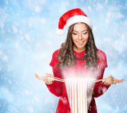 Beautiful young woman looking at a gift bag. On snowy background Royalty Free Stock Photos