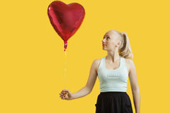 Beautiful young woman looking at heart shaped balloon over yellow background Royalty Free Stock Image