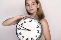 Beautiful young woman looking at a large silver retro clock that she is holding Royalty Free Stock Photo