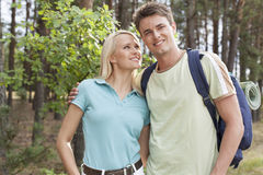 Beautiful young woman looking at man while hiking in forest Stock Photo
