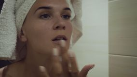 Young woman applying foundation cream after morning shower. stock footage