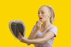Beautiful young woman looking at mirror while applying lipstick over yellow background Royalty Free Stock Photo