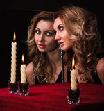 Beautiful young woman looking in the mirror near three candles. Over black background Stock Image