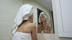 Young woman looking at mirror and touching face after morning shower. stock video
