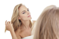Beautiful young woman looking into the mirror while touching her Royalty Free Stock Photo