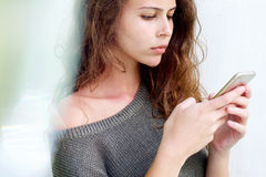 Beautiful young woman looking at mobile phone Stock Image