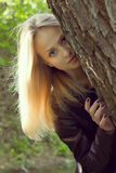 Beautiful young  woman looking out of a tree Stock Photos