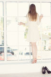 Beautiful young woman is looking out window Stock Photography