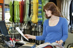 Beautiful young woman looking a paper while selecting textile sample in store Stock Photos