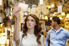 Beautiful young woman looking at price tag with man browsing in background Royalty Free Stock Image