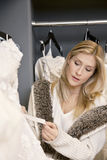 Beautiful young woman looking at price tag of wedding dress in bridal store Royalty Free Stock Image