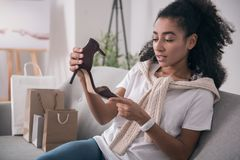 Beautiful young woman looking at the shoes. Perfect shoes. Beautiful young woman holding the shoes while looking at them Stock Photos
