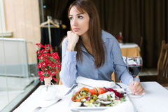 Beautiful young woman looking sideways in the restaurant. Stock Photo