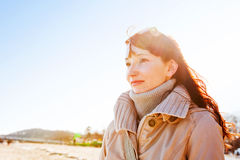 Beautiful young woman looking at the sky, sunny day. Beautiful young woman looking at the sky during a relaxing walk on the beach on a sunny day royalty free stock image