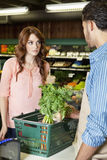 Beautiful young woman looking at store clerk in supermarket. Beautiful young women looking at store clerk in supermarket Stock Photography