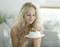 Beautiful young woman looking at tempting cake in house Royalty Free Stock Photography