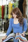 Beautiful young woman looking at textile samples in store Royalty Free Stock Photo