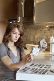 Beautiful young woman looking at tile samples in model home Stock Image