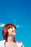 Beautiful young woman looking upwards at the blue sky Royalty Free Stock Photography