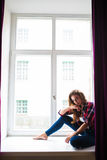 Beautiful young woman looking through window while sitting at windowsill at home Stock Photo