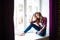 Beautiful young woman looking through window while sitting at windowsill at home Royalty Free Stock Images