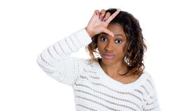 Beautiful young woman looking at you showing loser sign Stock Photos