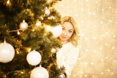 Beautiful young woman looks for a Christmas tree stock photos