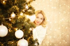 Beautiful young woman looks for a Christmas tree stock image