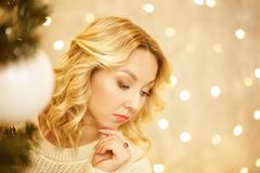Beautiful young woman looks for a Christmas tree royalty free stock images