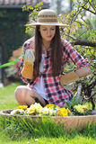 Beautiful young woman looks at flowers in garden Stock Photography