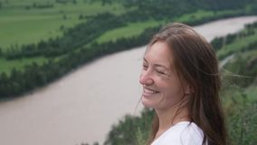 Beautiful young woman looks at the river from the top of the mountain. Summer Trekking in Wildlife Locations stock footage