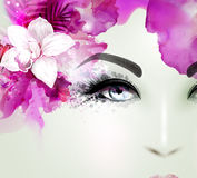 Beautiful young woman looks straight. Light blooming orchid decorated abstract hair. Royalty Free Stock Image