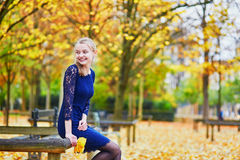 Beautiful young woman in the Luxembourg garden of Paris on a fall day. Beautiful young woman in blue dress in the Luxembourg garden of Paris on a fall day stock image