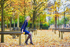 Beautiful young woman in the Luxembourg garden of Paris on a fall day. Beautiful young woman in blue dress in the Luxembourg garden of Paris on a fall day stock photo