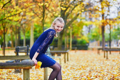 Beautiful young woman in the Luxembourg garden of Paris on a fall day. Beautiful young woman in blue dress in the Luxembourg garden of Paris on a fall day stock photos
