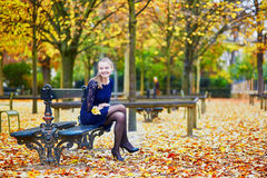 Beautiful young woman in the Luxembourg garden of Paris on a fall day. Beautiful young woman in blue dress in the Luxembourg garden of Paris on a fall day royalty free stock image
