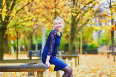 Beautiful young woman in the Luxembourg garden of Paris on a fall day. Beautiful young woman in blue dress in the Luxembourg garden of Paris on a fall day royalty free stock photography