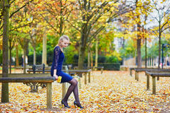 Beautiful young woman in the Luxembourg garden of Paris on a fall day. Beautiful young woman in blue dress in the Luxembourg garden of Paris on a fall day stock photography
