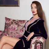 Beautiful young woman. On a luxurious couch Stock Photo
